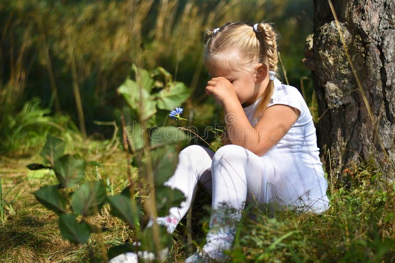 Lonely sad little girl in a white dress and a flower in her hand was lost in the woods, sitting near a tree and crying during day royalty free stock photography