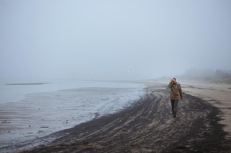 Lonely sad man walking on a foggy beach royalty free stock images