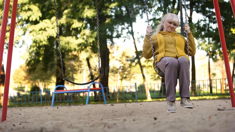 Lonely sad old woman riding on swing in park, no friends and family, abandoned. Stock photo stock photography