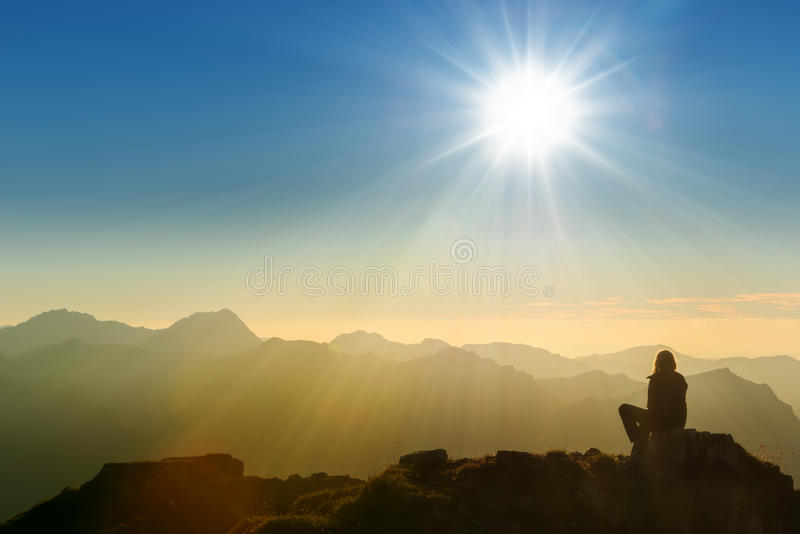 Lonely sad person sitting on mountain. Summit at dawn stock photos