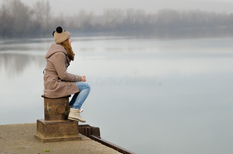 Lonely sad teenage girl sitting on dock on cold winter day stock photo