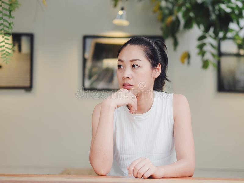 Lonely and sad woman is waitting for someone in the cafe. Lonely and sad Asian woman is waitting for someone in the cafe stock images