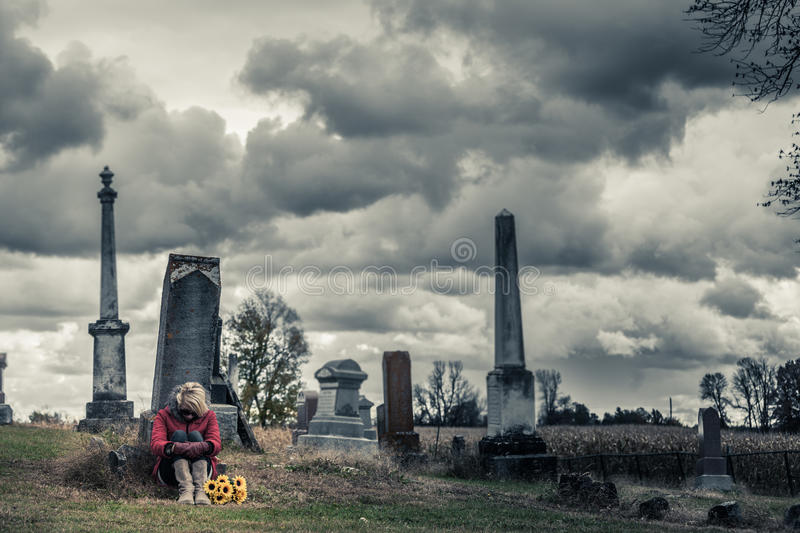 Lonely Sad Young Woman in Mourning in front of a Gravestone. Lonely Sad Young Woman in Mourning with Sunflowers in front of a Gravestone in a Cemetery stock image