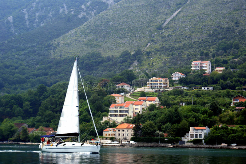 Lonely sail. A picturesque sea-view with a sailing yacht near Kotor, Montenegro royalty free stock photo
