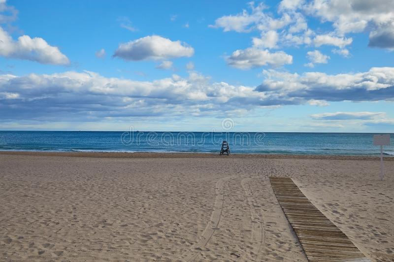 Lonely sandy beach with a lifeguard and a boardwalk to the sea on the Costa Blanca Spain royalty free stock photo
