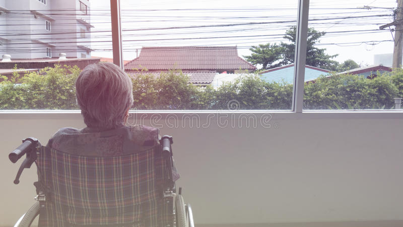Lonely senior looking through window in building - age, loneliness and people concept. Lonely senior woman looking through window in building - age, loneliness royalty free stock photos
