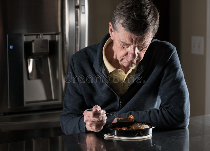 Lonely senior man eating ready meal at table. Lonely and depressed senior male sitting alone at kitchen table eating a microwaved ready meal of curry from royalty free stock photos