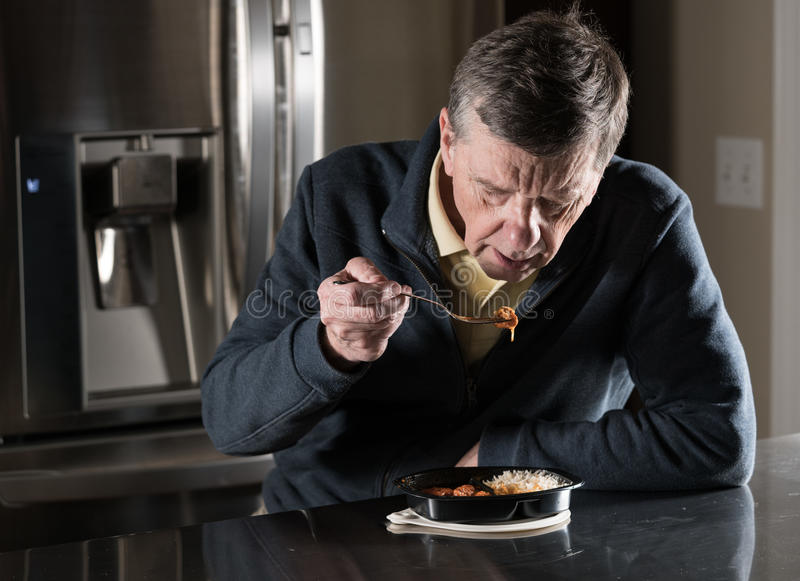 Lonely senior man eating ready meal at table. Lonely and depressed senior male sitting alone at kitchen table eating a microwaved ready meal of curry from royalty free stock photography