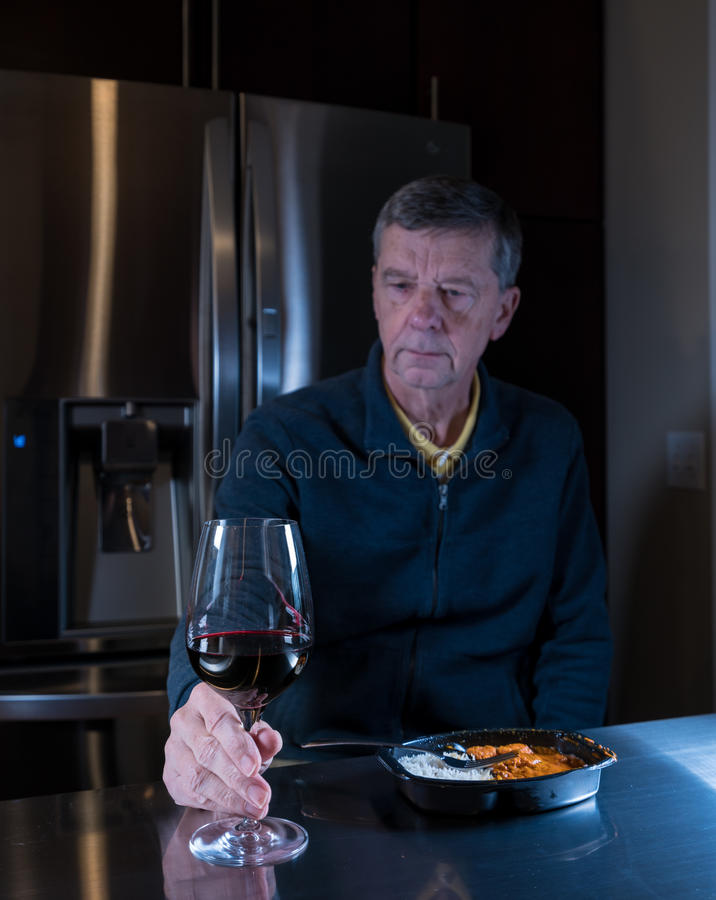 Lonely senior man eating ready meal at table. Lonely and depressed senior male sitting alone at kitchen table eating a microwaved ready meal of curry with red stock images