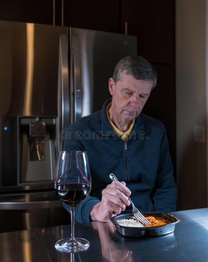 Lonely senior man eating ready meal at table. Lonely and depressed senior male sitting alone at kitchen table eating a microwaved ready meal of curry with red royalty free stock image