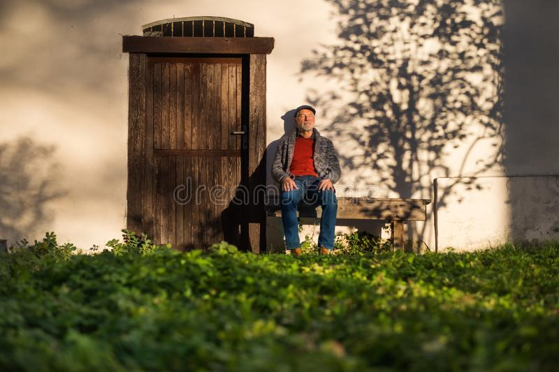 Lonely senior man sitting on bench in front of old house, eyes closed. A lonely senior man sitting on bench in front of old house, eyes closed stock photography