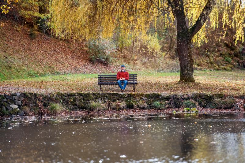 Lonely senior man sitting on bench by lake in nature, looking at camera. royalty free stock photo