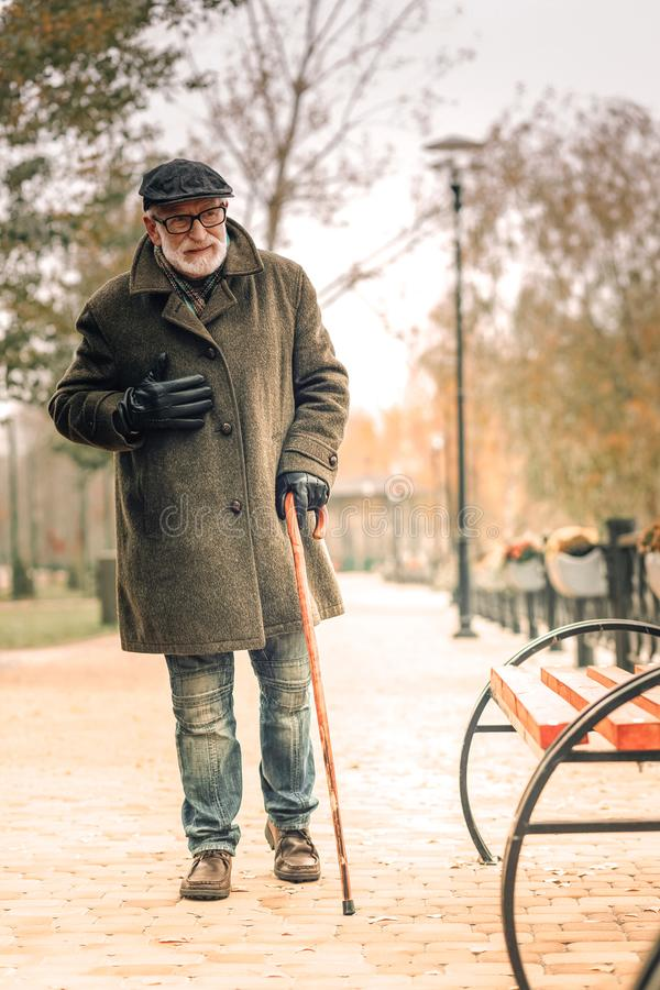 A lonely senior man walking in park experiencing chest pain. On a gloomy day stock photo