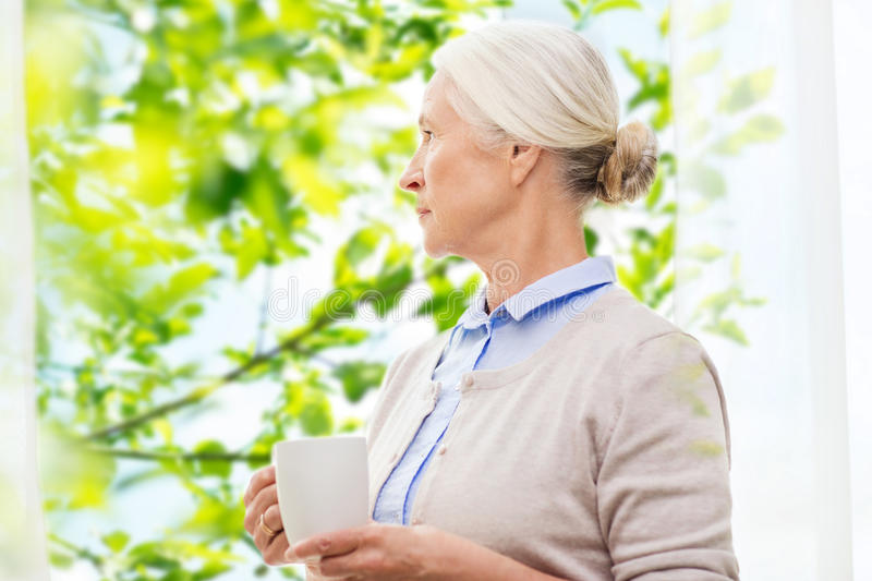 Lonely senior woman with cup of tea or coffee stock photos