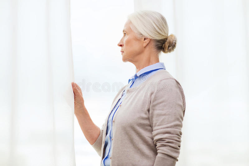 Lonely senior woman looking through window at home stock photography