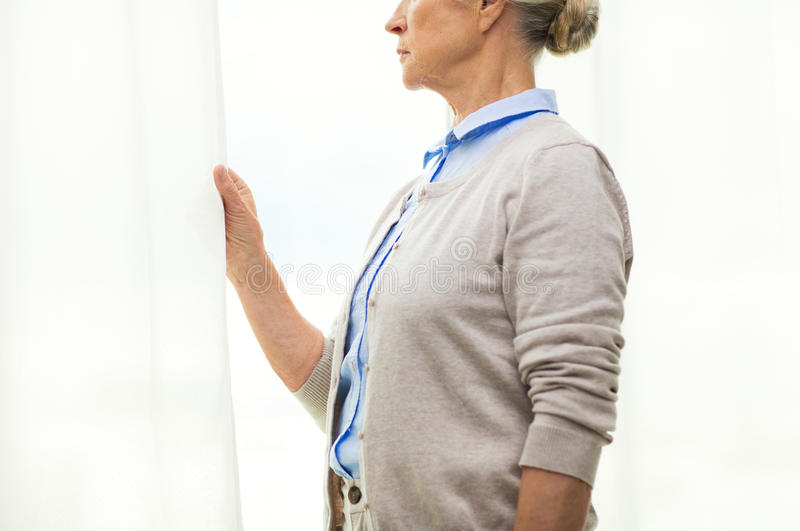 Lonely senior woman looking through window at home stock photos