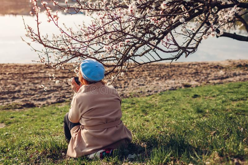 Lonely senior woman relaxing in spring garden. Mother`s day concept stock photography