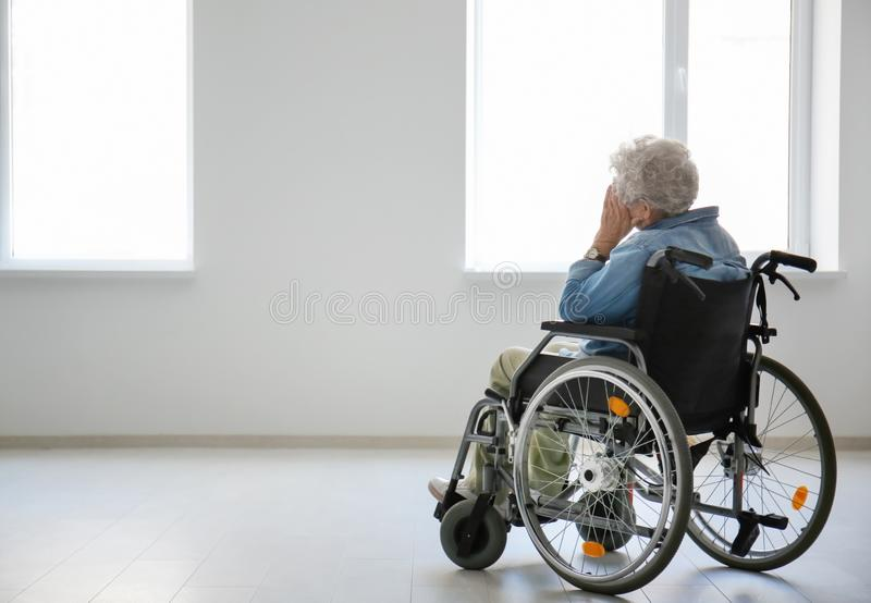 Lonely senior woman in wheelchair indoors royalty free stock photos