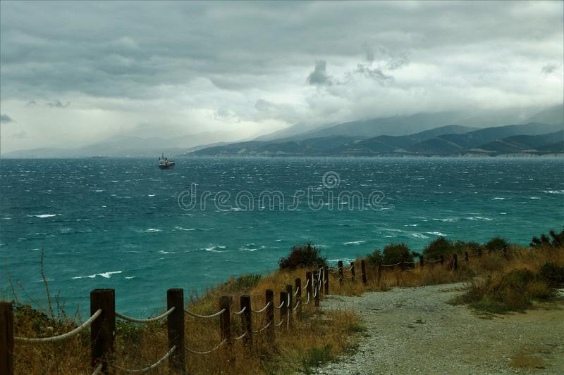 Lonely ship in the stormy sea. A strong wind blows on the Black Sea. The storm begins. A lonely ship hurries to return to the pier royalty free stock photos