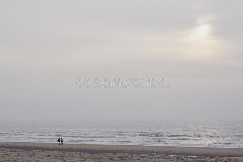 Silhouettes of two people walking along the cold winter shore of the north sea at sunset royalty free stock photos