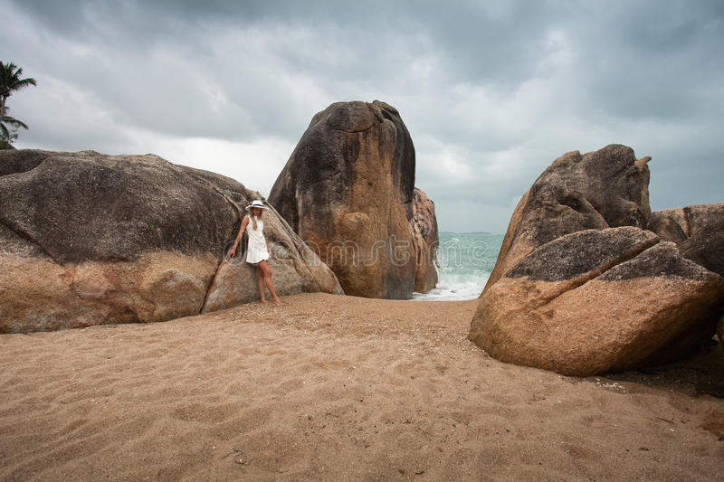 Lonely slender woman on a deserted beach on the background of large stones and a dark cloudy sky. royalty free stock image