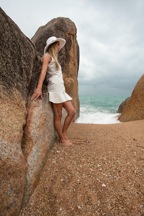 Lonely slender woman on a deserted beach on the background of large stones and a dark cloudy sky. stock image