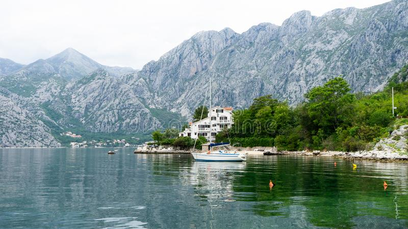 Lonely small boat in a fisherman village in the bay of Kotor. Lake surrounded by grey big mountains and green brushes. Landscape. With clouds, outdoor, tourism stock photo