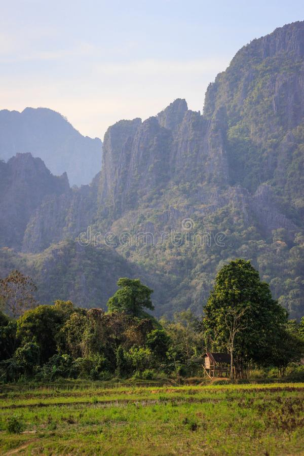 A lonely small wooden hut on a farm in Laos amid karst mountains stock image