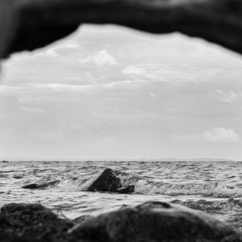 The lonely stone, which despite the water. In black and white royalty free stock photo