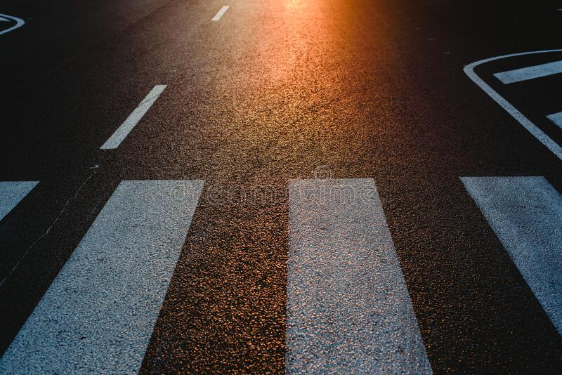 Lonely street with pedestrian crossing at sunset, texture with space for text.  royalty free stock photos