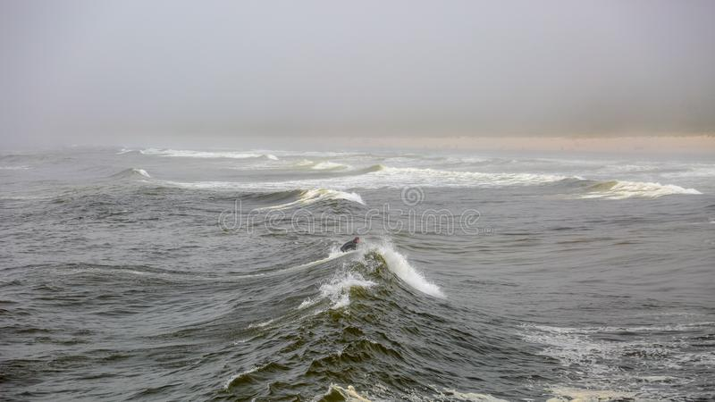 Lonely surfer catching a wave on a cold gloomy day stock photos