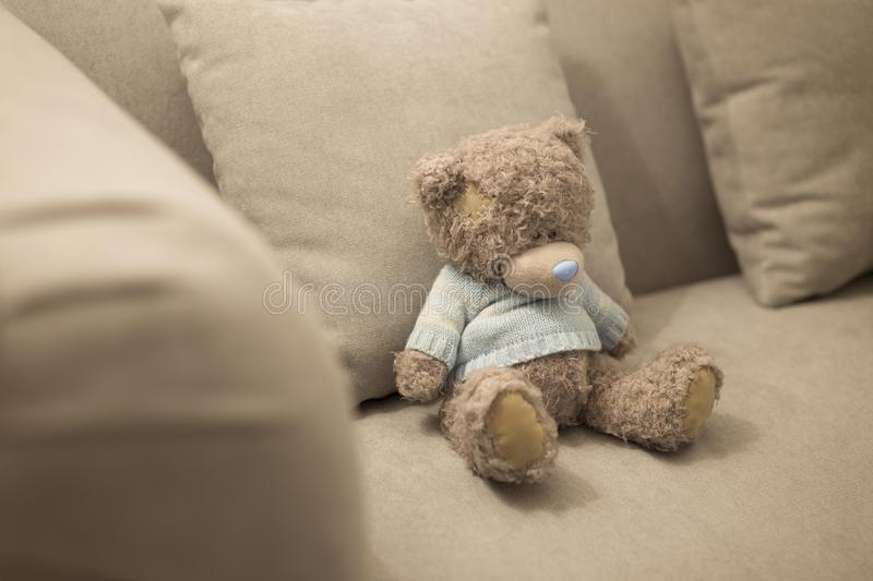 Lonely teddy bear is on the brown sofa. Lonely doll royalty free stock photo