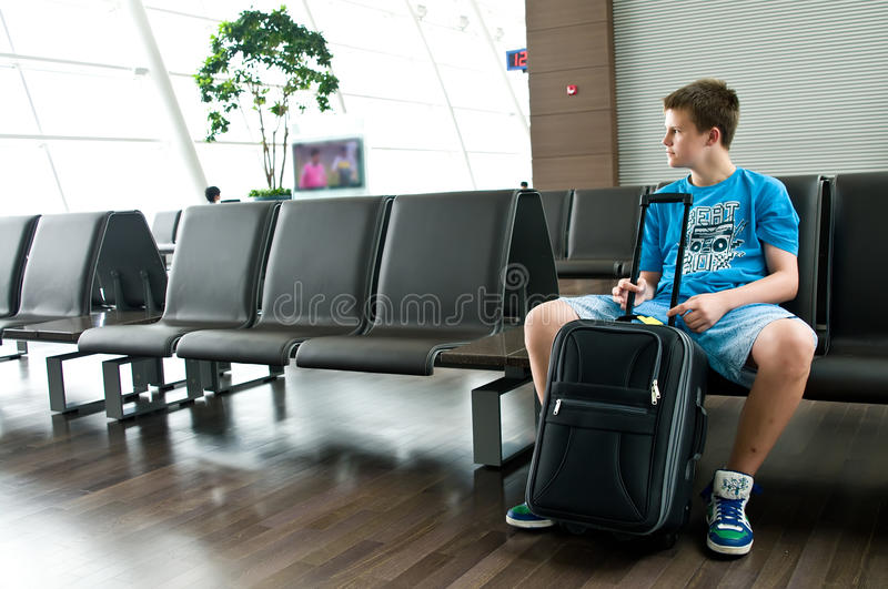 Lonely teen boy at airport. A lonely teenage boy sitting in a lounge of an airport royalty free stock images