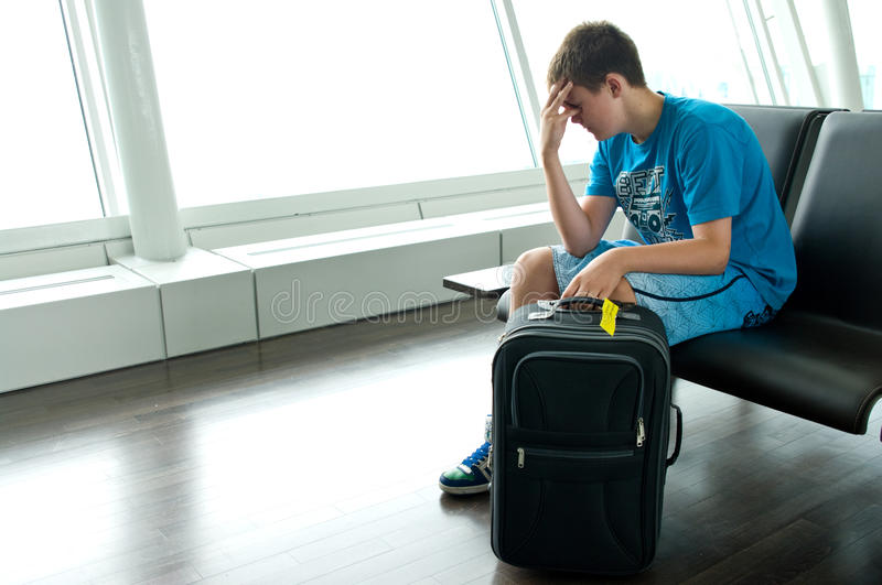 Lonely teen boy at airport. A lonely teenage boy sitting in a lounge of an airport stock image