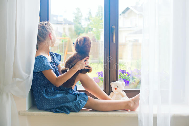 Lonely toddler russian girl sitting near window at home playing stock photos
