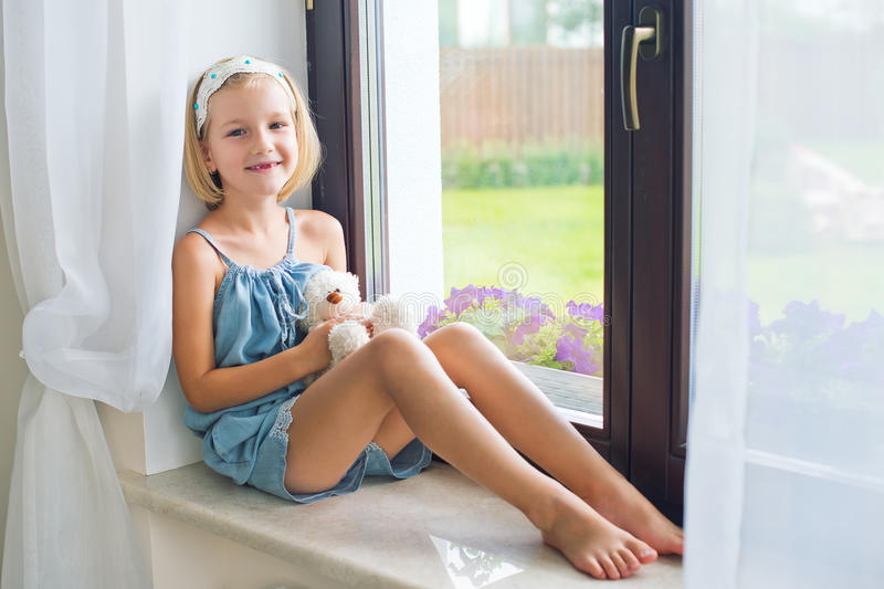 Lonely toddler russian girl sitting near window at home playing royalty free stock photography