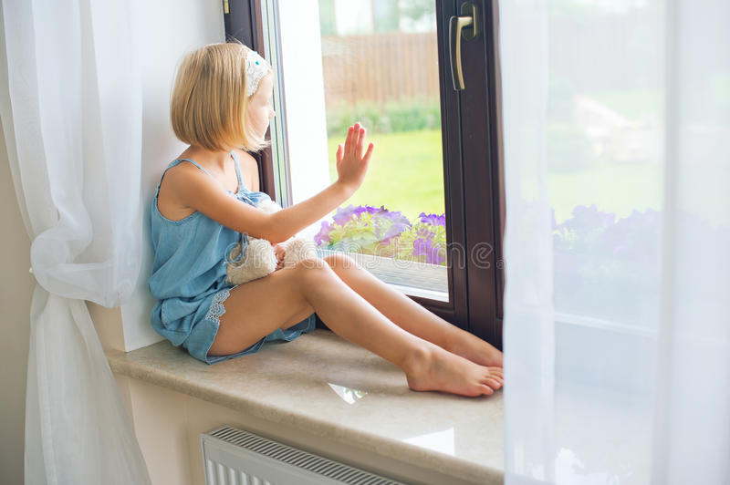 Lonely toddler russian girl sitting near window at home playing royalty free stock image