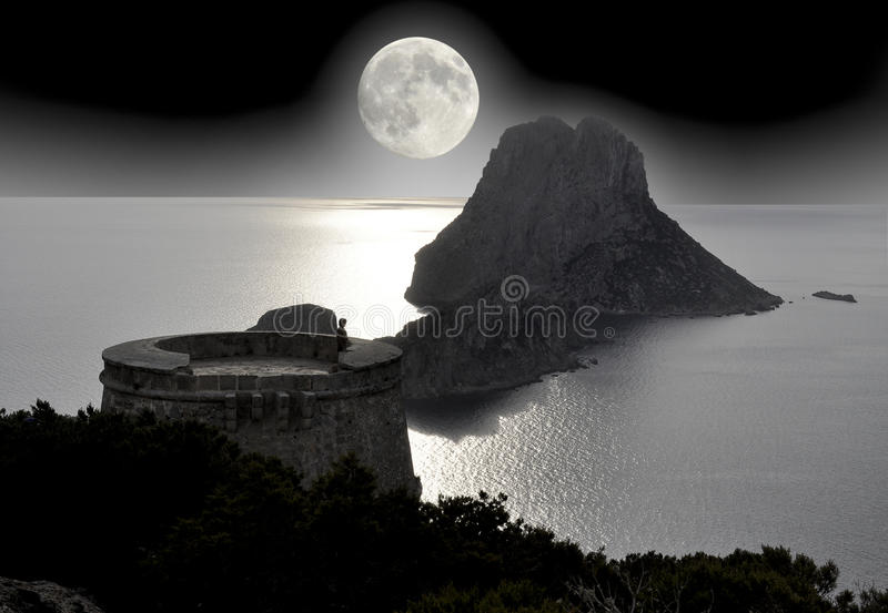 Lonely tourist looking full moon on the sea. Lonely tourist observes full moon on the sea from the tower of pirates in Ibiza royalty free stock photos
