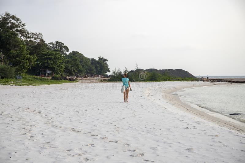 Lonely tourist on white sand beach by sea. Sole female tourist. Summer vacation on tropical island. stock photo