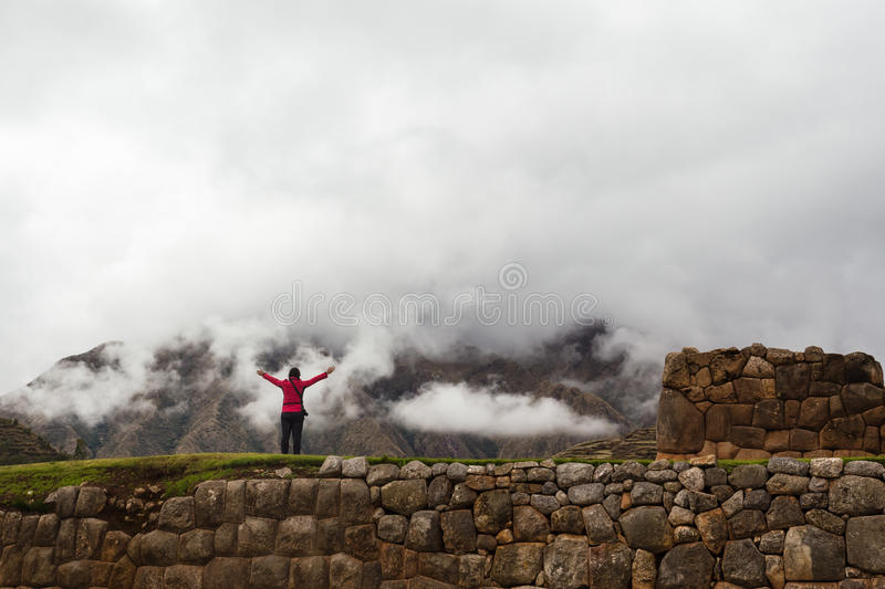 Lonely traveler in the ancient Inca wall. The figure of the lonely traveler in the ancient Inca wall in the province of Chinchero, Peru, the mountains in the stock photos