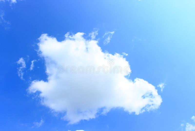 Cloud in the sky. Lonely white fluffy cloud in the light blue sky background on sunny day stock images