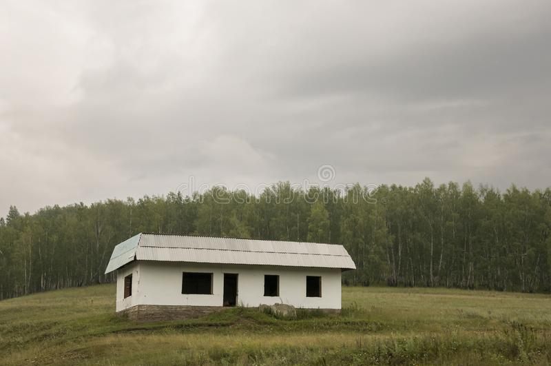 Lonely white forgotten building on the green mountain. Deep dark grey sky with a lot of clouds. Forest far away. Landscapes stock photos