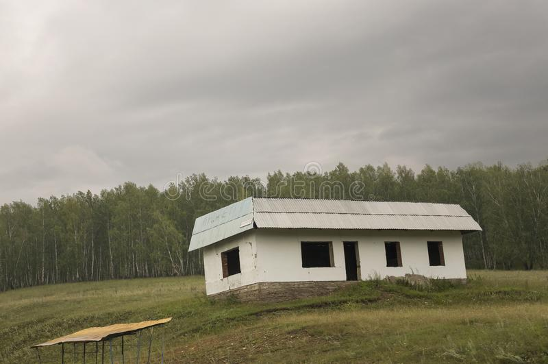 Lonely white forgotten building on the green mountain. Deep dark grey sky with a lot of clouds. Forest far away. Landscapes stock images