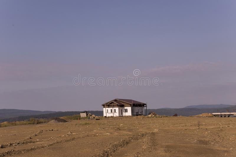 Lonely white forgotten building on the sand mountain. Deep calm blue sky with tints of purple. Ural landscapes. Brown colors. Like stock image