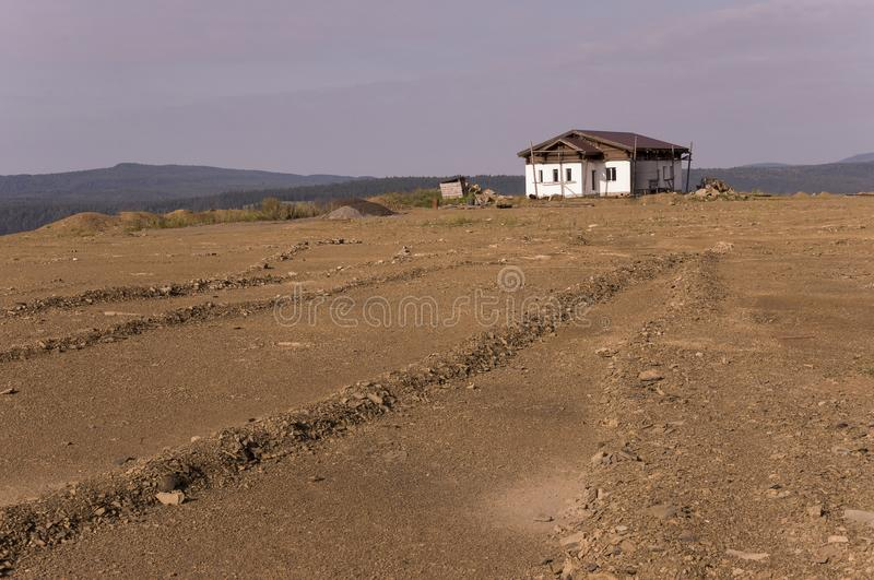 Lonely white forgotten building on the sand mountain. Deep calm blue sky with tints of purple. Ural landscapes. Brown colors. Like royalty free stock photography