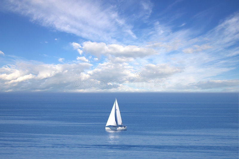 Lonely white sail at infinite ocean. On a photo: Lonely white sail at infinite ocean royalty free stock image