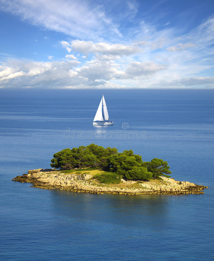 Lonely white sail near island. On a background of the blue sky with a clouds royalty free stock photo