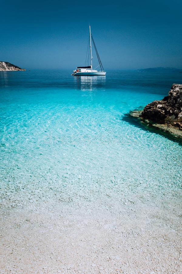 Lonely white sailing catamaran boat drift on calm sea surface. Pure azure clean blue lagoon with shallow water and stock images