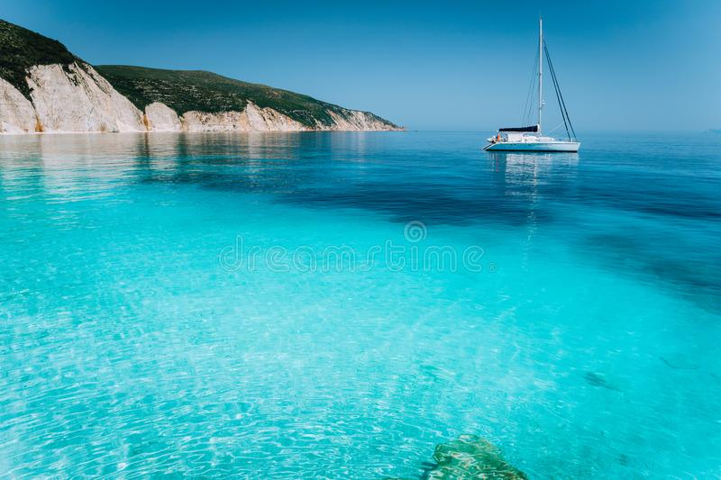 Lonely white sailing catamaran boat drift on calm sea surface. Pure shallow azure blue bay water of a beautiful beach stock images