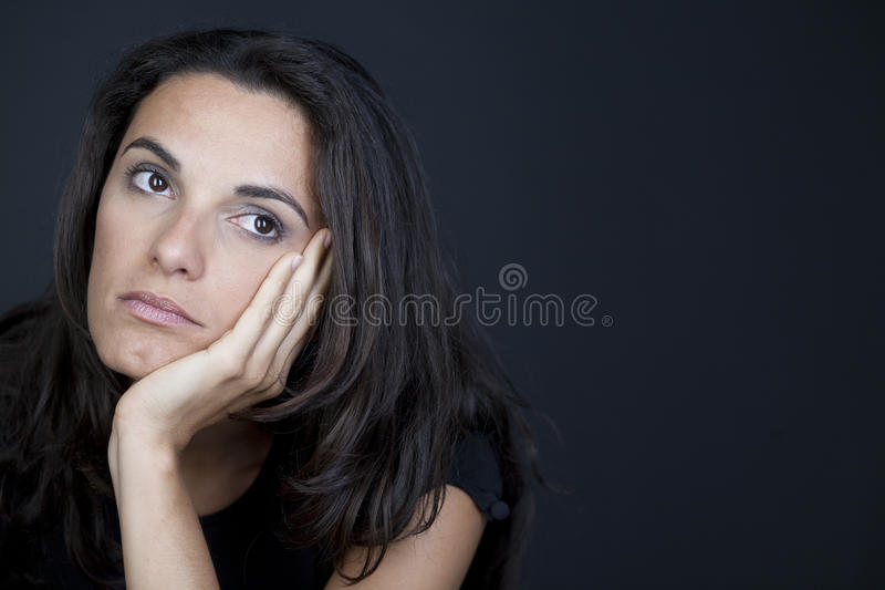 Lonely wife. Dark-haired beautiful woman being lonely on black background royalty free stock photos